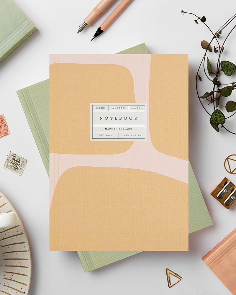 Vaaleanpunaista ja keltaista abstraktia kuviota muistikirjan kannessa