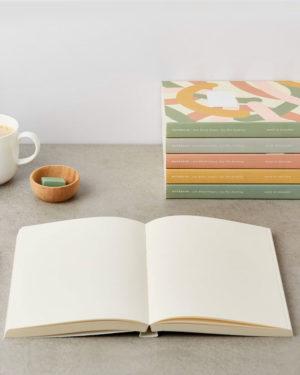 muistikirjan tyhjä aukeama ja kirjapino