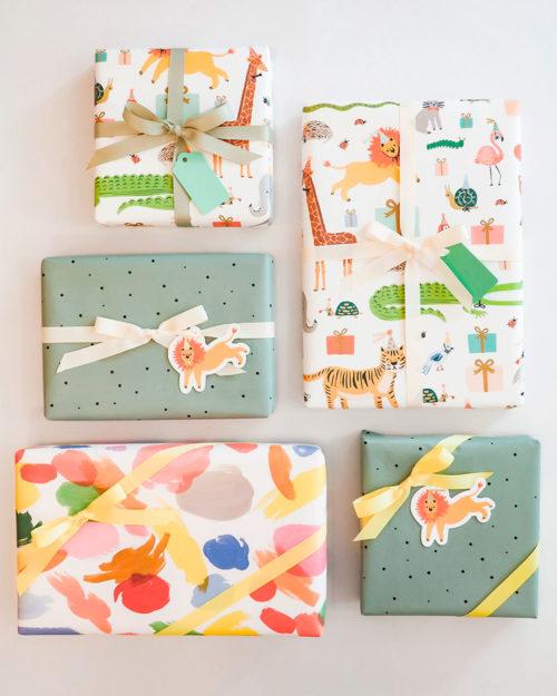 värikkäitä lahjapapereita, eläinkuviollisia pakettikortteja ja lahjanauhoja