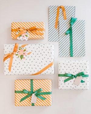 Raidallista ja pilkullista lahjapaperia, kukkakuvioisia pakettikortteja ja lahjanauhoja